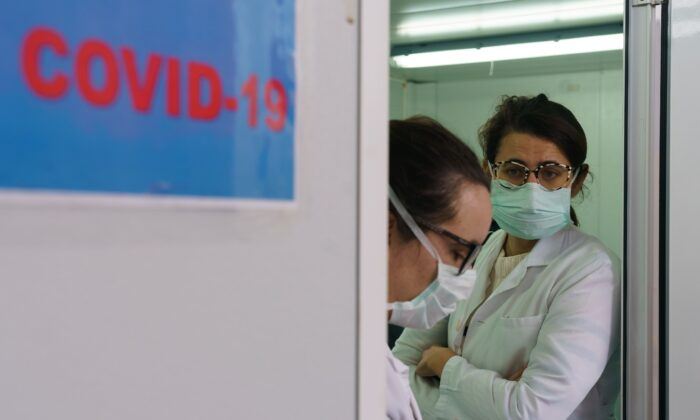 Health workers wait at the external screening area of the Burgos Hospital set up in order to separate patients with suspected CCP virus symptoms from the rest of the patients ahead of their admission in Burgos in northern Spain on April 2, 2020. (Cesar Manso/AFP via Getty Images)