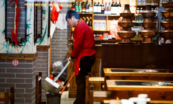 A waiter cleans the floor of a restaurant after closing hours in Beijing, China on Oct. 28, 2019. (Thomas Peter/Reuters)