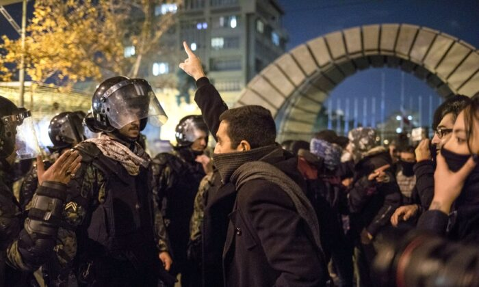 An Iranian man confronts riot police during a demonstration outside Tehran's Amir Kabir University on Jan. 11, 2020, after Iran admitted to having shot down a Ukrainian passenger jet by mistake on Jan. 8, killing all 176 people on board. (-/AFP via Getty Images)