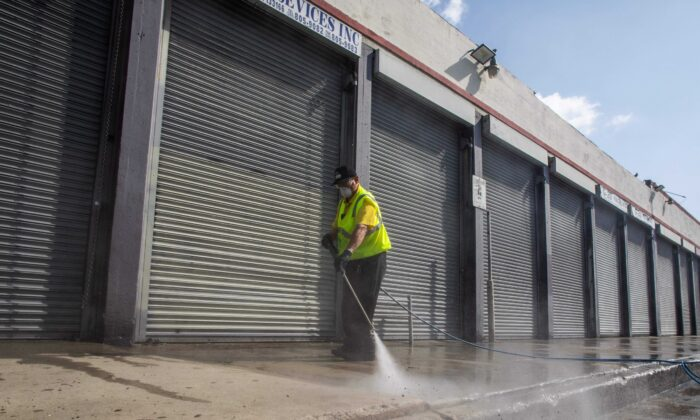 A member of the LA Fashion District Clean Team disinfects a side walk in the Fashion District in Downtown Los Angeles, Calif., on April 2, 2020. (Apu Gomes/AFP via Getty Images)