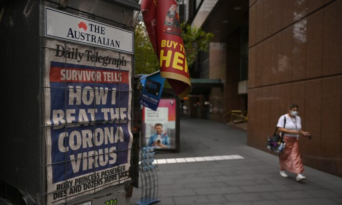 A newspaper headline about the coronavirus outbreak is seen on a near-deserted street in Sydney on March 30, 2020. (PETER PARKS/AFP via Getty Images)