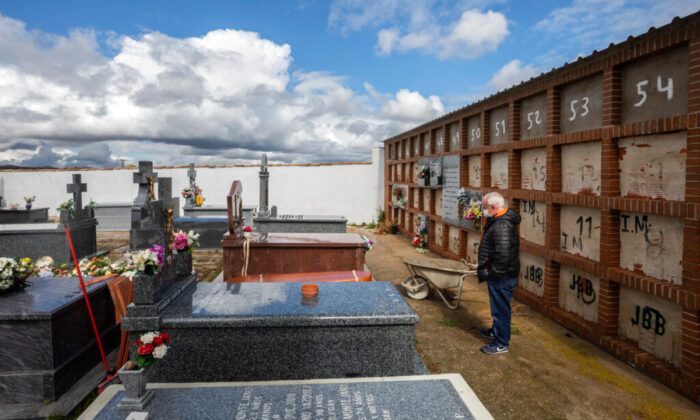 Julian Fernandez Mascaraque, 59, attends the burial of his mother Rosalia Mascaraque, 86, during the coronavirus outbreak in Zarza de Tajo, central Spain, on April 1, 2020. (Bernat Armangue/AP Photo)