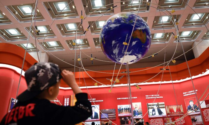 A boy looks at the BeiDou Navigation Satellite System at an exhibition marking the 40th anniversary of China's reform and opening up at the National Museum of China in Beijing, on Feb. 27, 2019. (Wang Zhao/AFP via Getty Images)