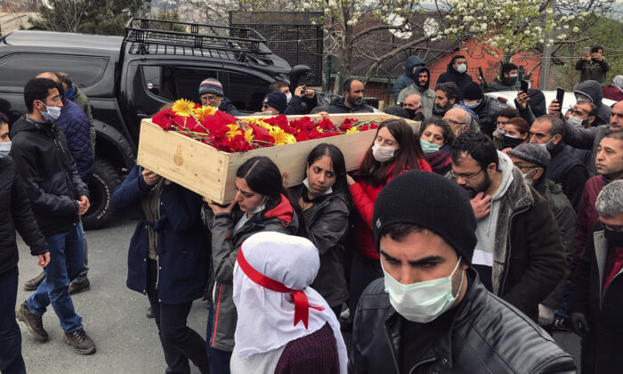 Mourners carry the open coffin of Helin Bolek, a member of a music group that is banned in Turkey, during the funeral procession in Istanbul, on April 3, 2020. (Ibrahim Mase/DHA via AP)