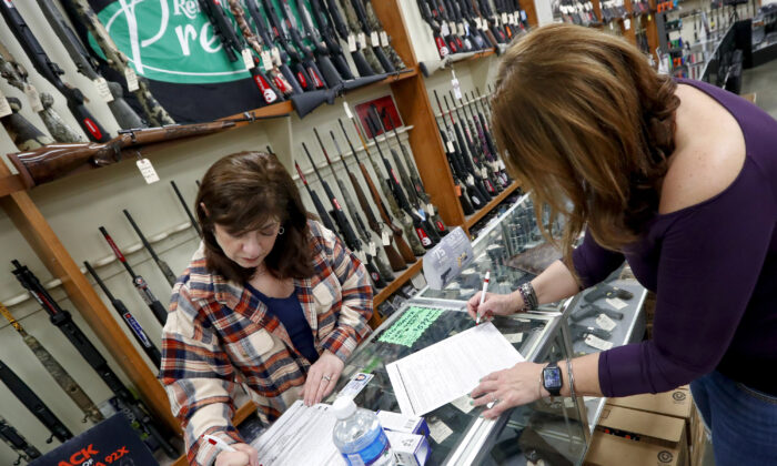 Andrea Schry (R) fills out the buyer part of legal forms to buy a handgun as shop worker Missy Morosky fills out the vendors parts after Dukes Sport Shop reopened in New Castle, Pennsylvania, on March 25, 2020. (Keith Srakocic/AP Photo)