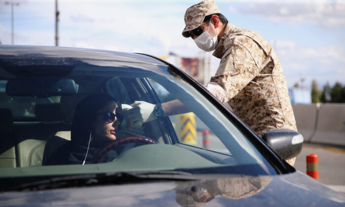 A member of the Islamic Revolution Guards Corps (IRGC) troops measures a temperature, following the outbreak of coronavirus disease (COVID-19) at the entrance of Qom, Iran March 24, 2020. (WANA (West Asia News Agency) via Reuters)