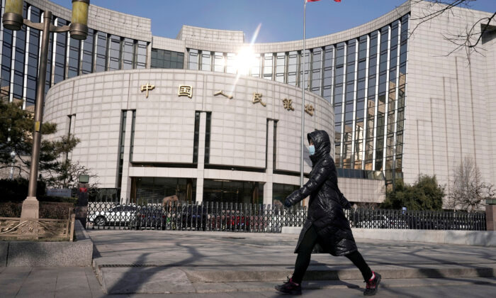 A woman wearing a mask walks past the headquarters of the People's Bank of China, the central bank, in Beijing, China, as the country is hit by an outbreak of the new coronavirus, on Feb. 3, 2020. (Jason Lee/Reuters)