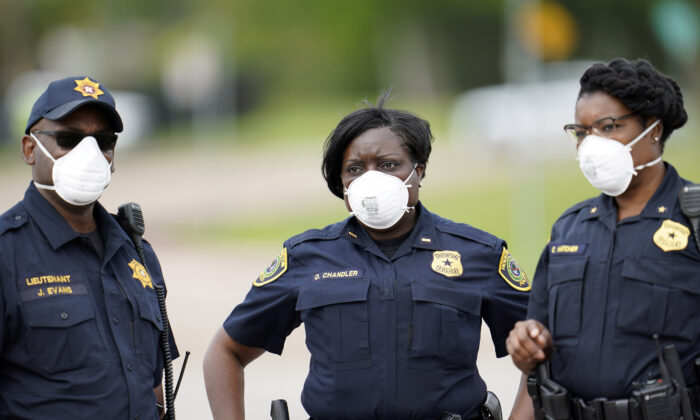 Law enforcement officers wear masks while working at a newly opened free drive-through CCP virus testing site provided by United Memorial Medical Center in Houston, Texas, on April 2, 2020. (David J. Phillip/AP Photo)