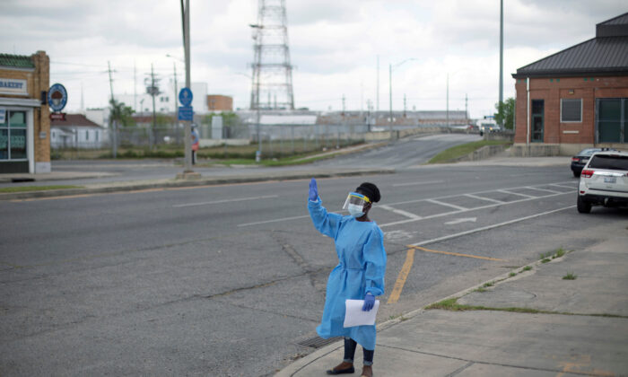 A staff member of Odyssey House Louisiana, which runs a drive-thru testing site for the CCP virus, waves to passing vehicles to try to alert the community about testing in New Orleans, Louisiana, on March 27, 2020. (Kathleen Flynn/Reuters)