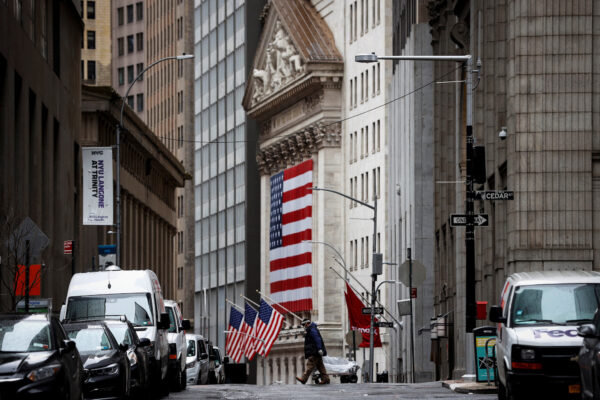 A man crosses a nearly deserted Nassau street in front of the New York Stock Exchange (NYSE) in the financial district of lower Manhattan in New York