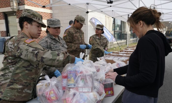 National Guard troops give food to residents of New Rochelle in Westchester County, N.Y., on March 12, 2020. (Timothy A. Clary/AFP via Getty Images)
