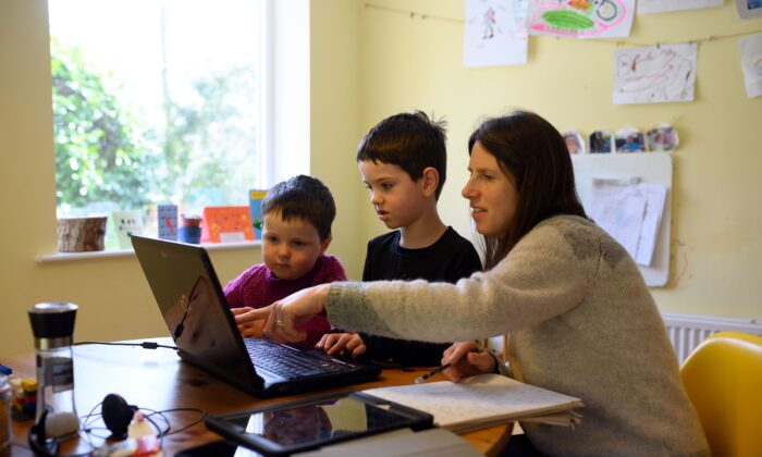 Children are assisted by their mother as they navigate online learning resources during pandemic lockdown measures in Huddersfield, England, on March 23, 2020. (Oli Scarff/AFP via Getty Images)