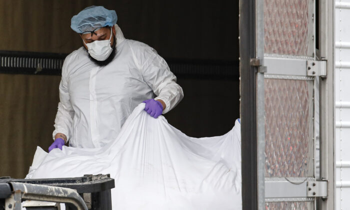 A body wrapped in plastic is loaded onto a refrigerated container truck used as a temporary morgue at Brooklyn Hospital Center in New York City, on March 31, 2020. (John Minchillo/AP Photo)