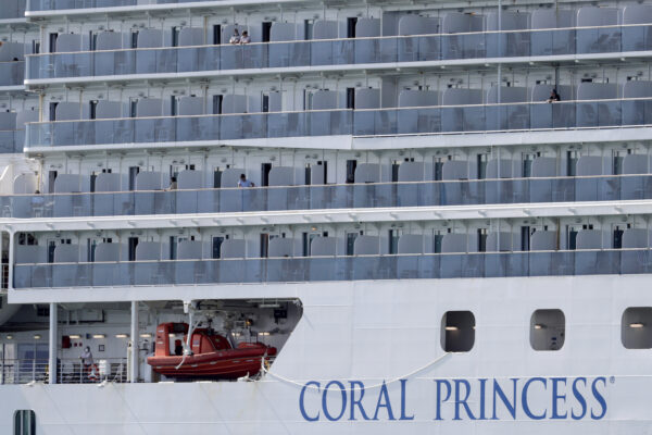 People look out from the Coral Princess cruise ship as it is docked