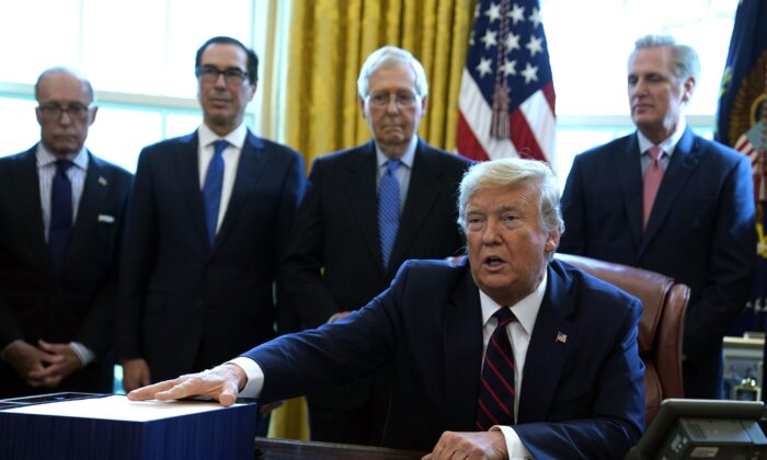 Then-President Donald Trump speaks before he signs the coronavirus stimulus relief package in the Oval Office at the White House on March 27, 2020. Listening are from left, Larry Kudlow, White House chief economic adviser, Treasury Secretary Steven Mnuchin, Senate Majority Leader Mitch McConnell (R-Ky.), and House Minority Leader Kevin McCarty (R-Calif.). (Evan Vucci/AP Photo)