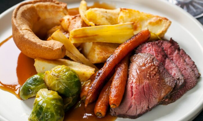 A typical Sunday roast consists of a nice cut of roast beef, potatoes and carrots, and Yorkshire puddings.