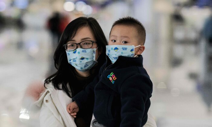 A woman and a child wearing protective masks walk toward check-in counters at Daxing international airport in Beijing on Jan. 21, 2020. (Nicolas Asfouri/AFP via Getty Images)