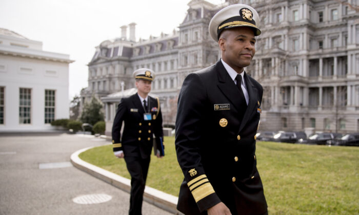 In this March 5, 2020, file photo, Surgeon General Jerome Adams, right, arrives to do an on camera interview outside the West Wing on the North Lawn of the White House in Washington. (Andrew Harnik/AP Photo)
