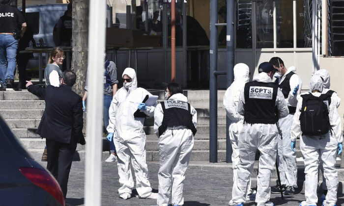 Police officers investigate after a man wielding a knife attacked residents venturing out to shop in the town under lockdown, in Romans-sur-Isere, southern France, on April 4, 2020. (AP Photo)