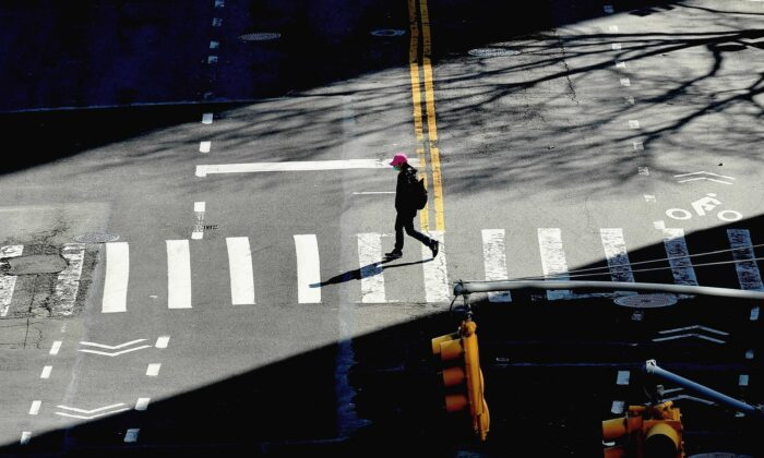 A person crosses the street in New York City on March 27, 2020. (Angela Weiss/AFP via Getty Images)