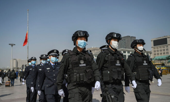Chinese police officers wear protective masks as they march in formation away from a national flag at half staff after observing three minutes of silence to mark the country's national day of mourning for COVID-19 at Beijing Railway Station in Beijing on April 4, 2020. (Kevin Frayer/Getty Images)