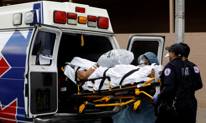 Healthcare workers load a person into an ambulance outside the Wyckoff Heights Medical Center during the outbreak of the CCP virus in the Brooklyn borough of New York City, New York, on April 4, 2020. (Andrew Kelly/Reuters)