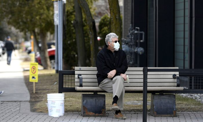 A man wears a mask for protection against COVID-19 while waiting outside a store in Ottawa, Canada, on April 4, 2020. (The Canadian Press/Justin Tang)