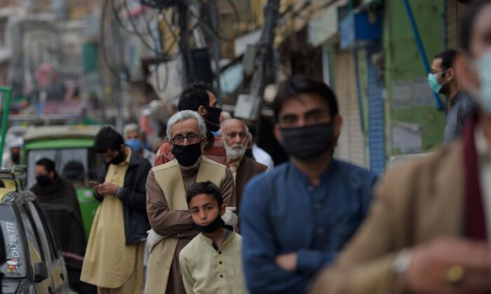Pakistani peoples line up to pay utility bills in a bank during a government-imposed nationwide lockdown as a preventive measure against the COVID-19 coronavirus in Rawalpindi on March 30, 2020. (FAROOQ NAEEM/AFP via Getty Images)