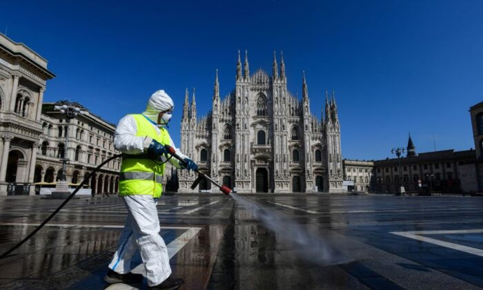 An employee wearing protective gear, working for environmental services company AMSA, sprays disinfectant on Piazza Duomo in Milan, on March 31, 2020 during the country's lockdown aimed at curbing the spread of the COVID-19 infection, caused by the novel coronavirus. (Piero Cruciatti/AFP via Getty Images)
