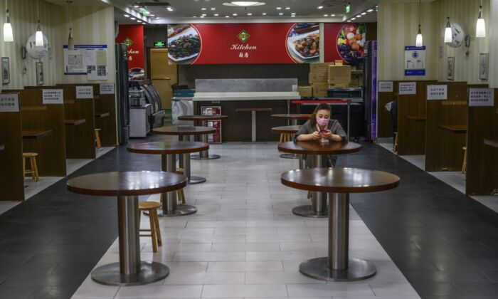 A Chinese woman waits for customers in a nearly empty restaurant at a shopping mall in Beijing, China on March 26, 2020. (Kevin Frayer/Getty Images)