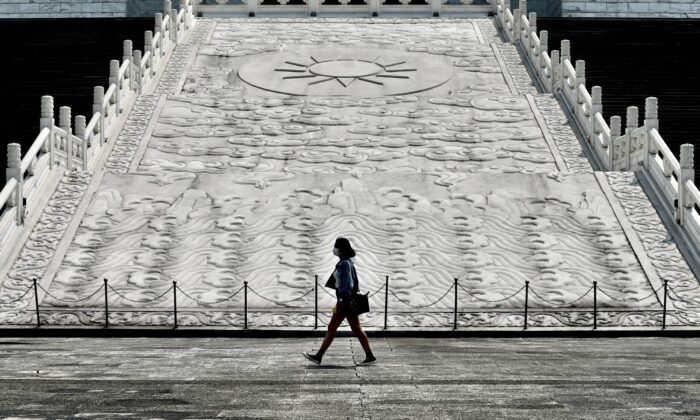 A woman wearing a face mask, amid concerns of the coronavirus, walks in front of Chiang Kai-shek Memorial Hall in Taipei, Taiwan, on March 31, 2020. (Sam Yeh/AFP via Getty Images)