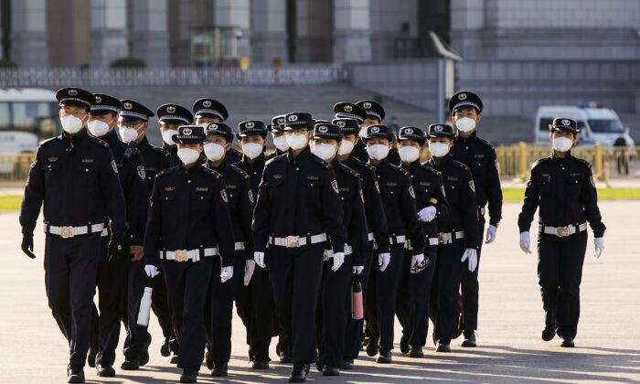 Chinese security personnel wearing protective masks march through Tiananmen Square in Beijing, China, on April 04, 2020. (Lintao Zhang/Getty Images)