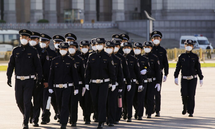 Chinese security personnel wearing protective masks march through Tiananmen Square during a national mourning of victims of COVID-19 in Beijing on April 4, 2020. (Lintao Zhang/Getty Images)