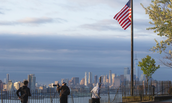 Flags are flying at half-mast as the sun rises in Manhattan on April 6, 2020, as seen from Weehawken, New Jersey. (Kena Betancur/Getty Images)