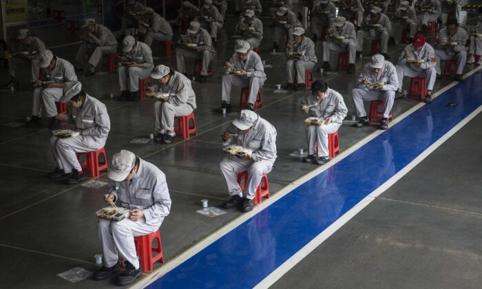 Employees eat their lunch while staying 2 meters away from each other at the Dongfeng Fengshen plant in Wuhan, Hubei Province, China, on March 24, 2020. (Getty Images)
