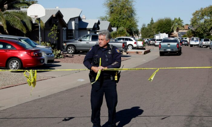 A Phoenix police officer connects crime scene tape together outside the scene of a deadly shooting, in Phoenix, on March 30, 2020. (Matt York/AP Photo)