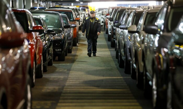 A Hertz Car Rental employee walks between rows of unused rental cars at Toronto Pearson International Airport in Toronto, Canada, on April 1, 2020. (Cole Burston/Getty Images)