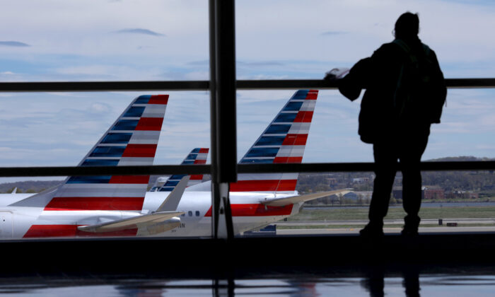 American Airlines planes are seen while a passenger waits for boarding at the Reagan International Airport in Washington on April 3, 2020. (Reuters/Carlos Barria)