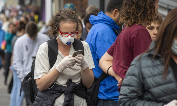 A woman in a mask is seen lining up at Centrelink in Bondi Junction on March 23, 2020 in Sydney, Australia. (Jenny Evans/Getty Images)