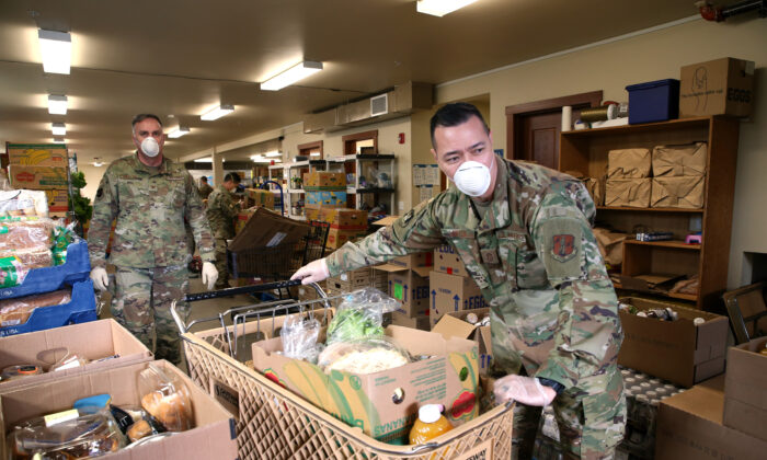 Chief Allan Lawson (R) and Colonel Gent Welsh, both from the Washington Air National Guard, help distribute food with volunteers at the Nourish Pierce County food bank set up at the Mountain View Lutheran Church in Edgewood, Washington, on April 4, 2020. (Karen Ducey/Getty Images)