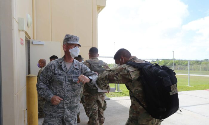 Maj. Dennis Kirkland, Guam National Guard state chaplain, greets Soldiers preparing to process through medical and customs checks at the GUNG readiness center after arriving on island April 5. (U.S. Army National Guard photo by JoAnna Delfin)