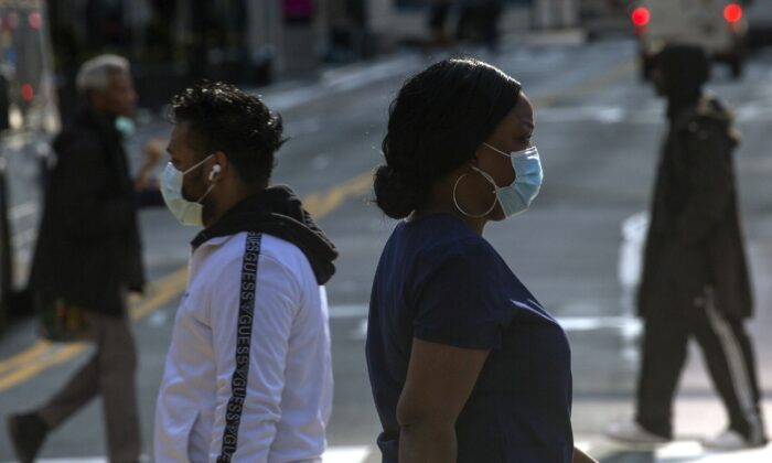 People wear masks as they walk along 34th Street in New York City on April 6, 2020. (Kena Betancur/Getty Images)