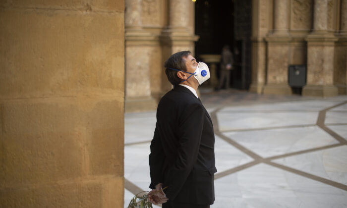 A security guard wearing a face mask and gloves holds a branch of olive tree before the celebration of the Palm Sunday mass at the Santa Maria de Montserrat abbey in Monistrol de Montserrat on April 5, 2020, (Josep Lago/AFP via Getty Images)