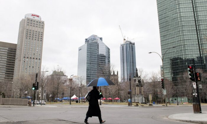 A woman crosses an empty street in downtown Montreal on April 5, 2020. (The Canadian Press/Graham Hughes)
