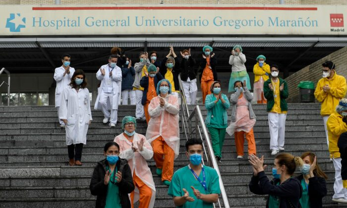 Staff members of the Gregorio Maranon Hospital applaud to pay tribute to cleaning workers in Madrid on April 1, 2020, during a national lock-down to prevent the spread of the new coronavirus. (Photo by Oscar Del Pozo/AFP/Getty Images)