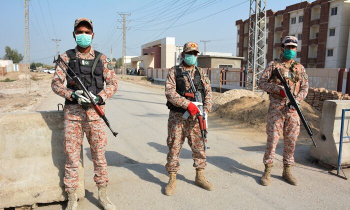 Soldiers in facemasks guard a road leading to a COVID-19 quarantine facility in Sukkur, Iran, on March 17, 2020. (Shahid Ali/AFP/Getty Images)