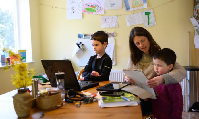 Leo (C), aged 6, and Espen, aged 3, are assisted by their mother Moira as they homeschool and navigate online learning resources provided by their infant school in the village of Marsden, near Huddersfield, northern England, on March 23, 2020. (Oli Scarff/AFP via Getty Images)