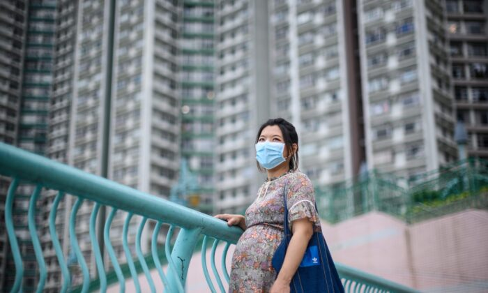 Expectant mother Jamie Chui, 33, poses in front of residential buildings near where she lives in Hong Kong, China, on March 31, 2020. (Anthony Wallace/AFP via Getty Images)