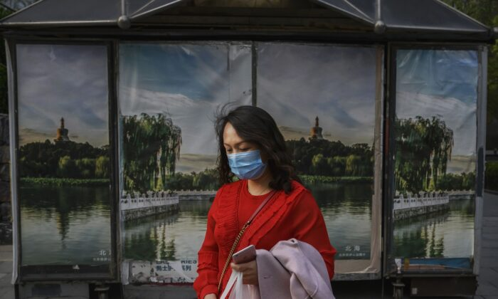 A Chinese woman wears a protective mask as she walks in the street in Beijing on April 7, 2020. (Kevin Frayer/Getty Images)