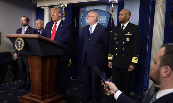 President Donald Trump speaks as top officials, including Dr. Robert Redfield, the CDC director (second from right) and Surgeon General Dr. Jerome Adams (R) listen in Washington on Feb. 29, 2020. (Alex Wong/Getty Images)